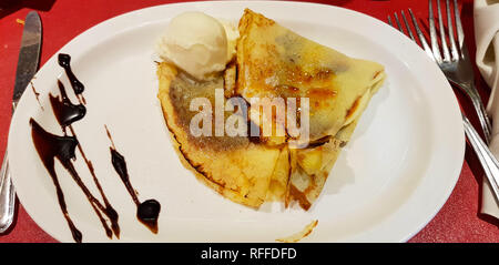Chocolate crepe with ice cream, El Calafate, Argentina. The crepe is a type of soft wafer, thin and not crunchy, cooked on a round red hot surface. - Stock Photo