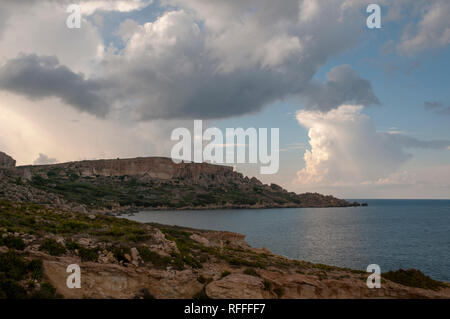 Dramatic coastal landscape on eastern Gozo, Malta. View over Dahlet Qorrot Bay and San Philip Bay and Sopu Tower in the distance. - Stock Photo