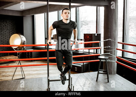 Young athletic man pulling up on the bar, warming up before the training on the boxing ring at the gym - Stock Photo
