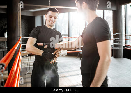 Boxing trainer winding bandage on the wrist for a man, preparing for the boxing on the boxing ring at the gym - Stock Photo