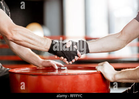 Close-up of a handshake of a two men before fighting at the boxing ring in the gym - Stock Photo