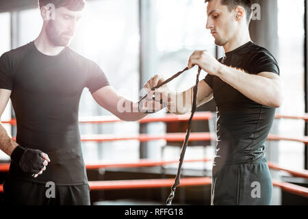 Trainer winding bandage on the wrist to a man, preparing for the boxing on the boxing ring at the gym - Stock Photo