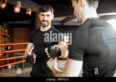 Trainer winding bandage on the wrist to a handsome bearded man, preparing for the boxing on the boxing ring at the gym - Stock Photo
