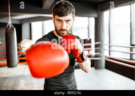 Portrait of an athletic man as a boxer in red boxing gloves on the fighting ring at the gym - Stock Photo