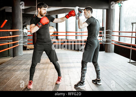 Boxing trainer showing to a man how to fight, teaching to box on the boxing ring at the gym - Stock Photo