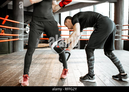 Boxing trainer keeping leg of a man learning how to fight correctly on the boxing ring at the gym - Stock Photo