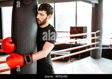Exhausted man hugging punching bag after the training on the boxing ring at the gym - Stock Photo