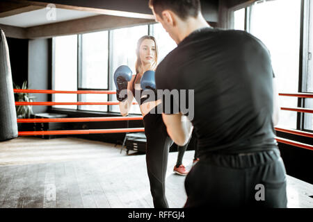 Young woman training to box with personal coach on the boxing ring at the gym - Stock Photo