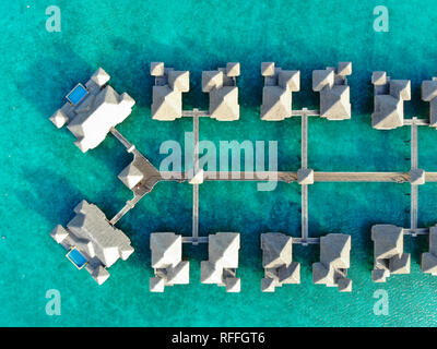 Aerial view of overwater bungalow villas with thatched roofs in the Bora Bora lagoon in French Polynesia - Stock Photo