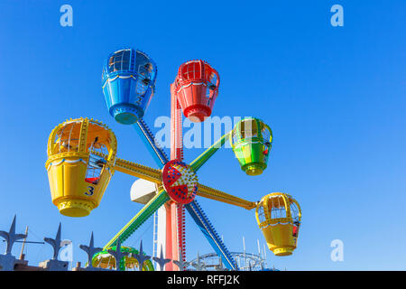 Brightly coloured ferris wheel ride at a funfair on Clarence Pier, Clarence Esplanade, Southsea, Portsmouth, UK - Stock Photo