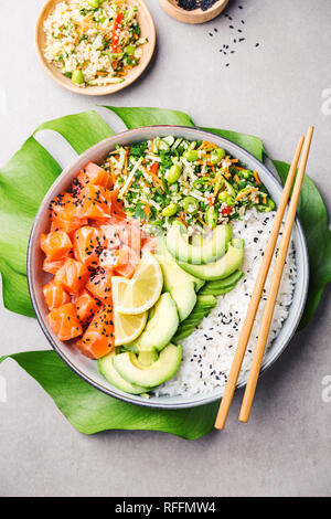 Tasty appetizing poke bowl served with salmon, avocado, rice, salad with edamame. Grey background. View from above. Vertical. - Stock Photo