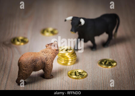 Cryptocurrency bitcoin bear and bull figures on a wooden table. Bearish or bullish market trend concept - Stock Photo