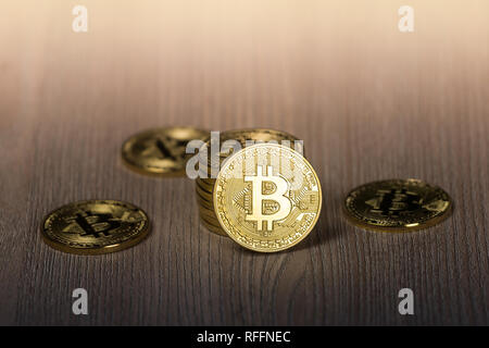 Bitcoin gold coins on a wooden table - Stock Photo