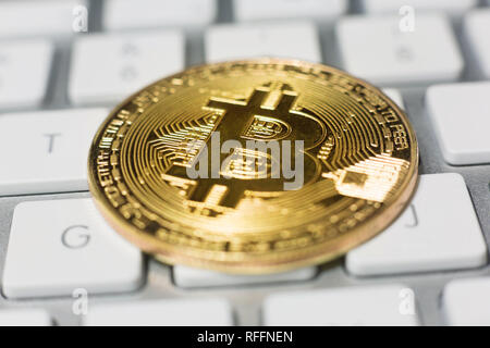 Bitcoin crypto coin placed on a minimalist white computer keyboard - Stock Photo