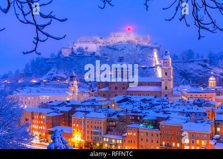 Salzburg, Austria: Heavy snow on the historic city of Salzburg with famous Festung Hohensalzburg and Salzach river in winter - Stock Photo