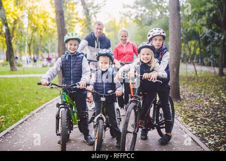 Theme family sports vacation in park in nature. big friendly Caucasian family of six people mountain bike riding in forest. Children brothers and sist