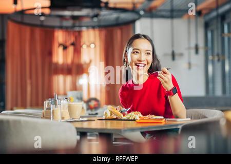 Dark-eyed woman feeling rested enjoying weekend breakfast - Stock Photo