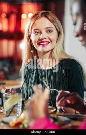 Blonde-haired woman with evening makeup having dinner - Stock Photo
