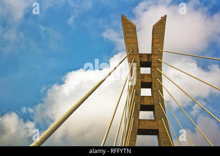 Section of a cable-stayed bridge against a vibrant blue sky with white clouds - Lekki-Ikoyi bridge, Lagos, Nigeria - Stock Photo