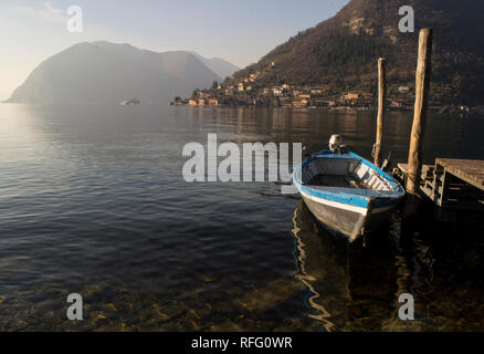 Little boat parked near a wooden pier on Iseo lake in Northern Italy, view on Monte Isola island. - Stock Photo