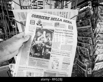PARIS, FRANCE - JUL 16, 2018: Man buying Corriere della sera newspaper announcing France champion title after French national football team won their  - Stock Photo
