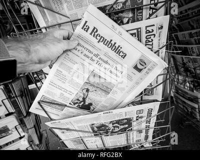 PARIS, FRANCE - JUL 16, 2018: Man buying Italian la Republica newspaper announcing France champion title after French national football team won their - Stock Photo