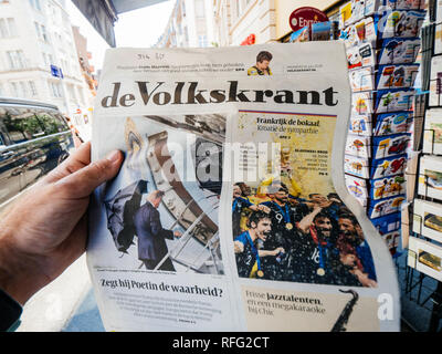 PARIS, FRANCE - JUL 16, 2018: Man buying De Volkskrant dutch newspaper announcing France champion title after French national football team won their  - Stock Photo
