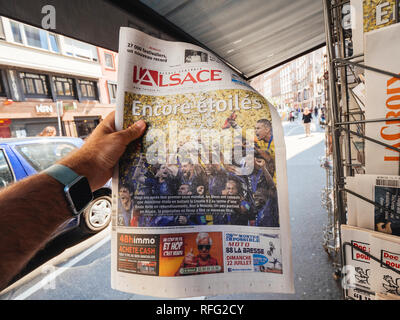 PARIS, FRANCE - JUL 16, 2018: Man buying L'Alsace newspaper announcing France champion title after French national football team won their FIFA World  - Stock Photo