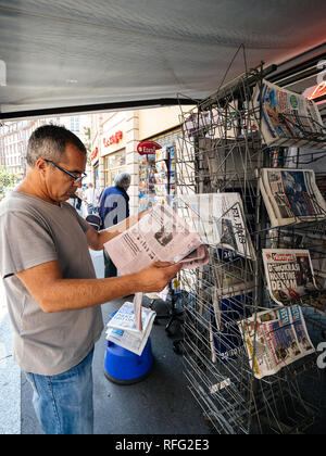 PARIS, FRANCE - JUL 16, 2018: Vertical smoking man buying  newspaper announcing France champion title after French national football team won their FI - Stock Photo