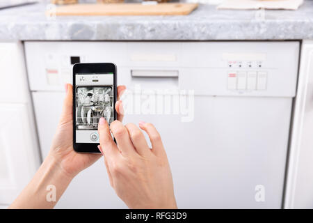 Close-up Of A Woman's Hand Operating Dishwasher With Mobile Phone - Stock Photo