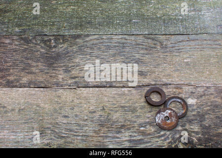 Weathered pallet wood boards as a background with rusty steel washers placed in the lower right corner. - Stock Photo