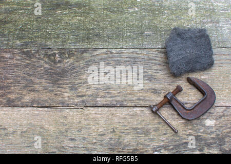 Weathered pallet wood boards as a background with steel wool and a rusty C clamp placed on the right side. - Stock Photo