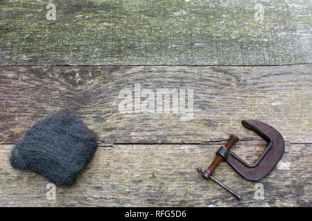Weathered pallet wood boards as a background with steel wool and a rusty C clamp placed along the bottom. - Stock Photo