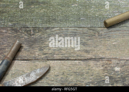 Weathered pallet wood boards as a background with rusty steel stock placed in the lower left corner and brass stock placed in the upper right corner. - Stock Photo
