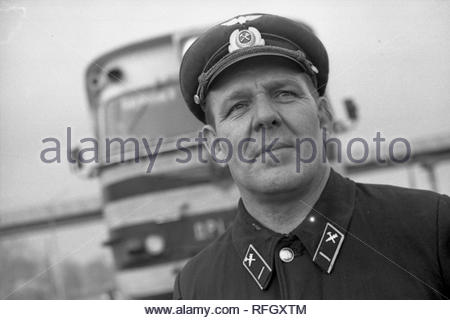 The portrait of train driver. The driver of the new diesel train is looking into distance. He dressed in uniform with peacked cap. The passeger diesel train is behind him. The train has just entered the service. - Stock Photo