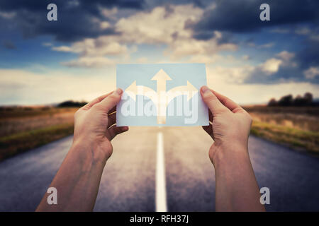 Hands holding paper with arrows crossroad symbol splitted in three different directions. Choose the correct way between left, right and front. Difficu - Stock Photo