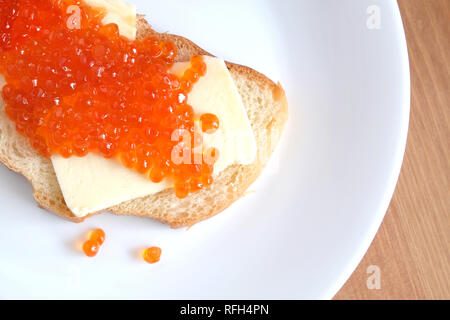 Sandwich with butter and red salmon caviar on white bread lies on white round plate on wooden table top view - Stock Photo