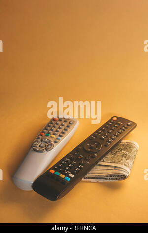 TV Remotes and US dollars on yellow background. Pay TV or television concept. - Stock Photo