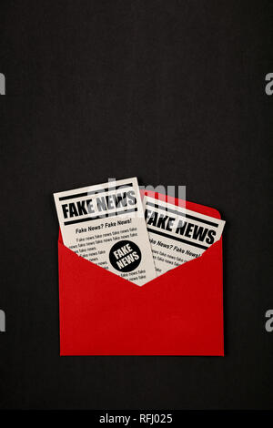 Close up brown paper mail envelope with FAKE NEWS newspapers over black background with copy space, elevated top view, directly above - Stock Photo