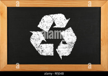 Black school chalkboard blackboard with chalk drawing of recycling logo icon in brown wooden frame - Stock Photo