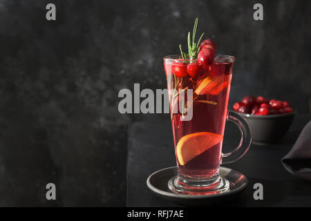 Cocktail cranberries and rosemary leaf on black background. - Stock Photo