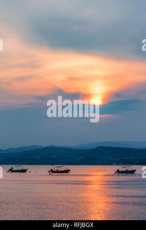 Sunset view of the Mediterranean sea and boats in Halkidiki, Greece. - Stock Photo