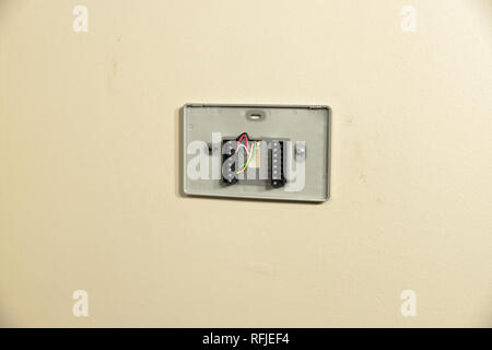Thermostat wiring plate on wall for installation - Stock Photo