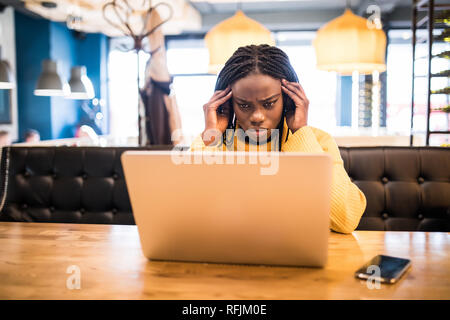 Young african woman with laptop suffering of headache while sitting in cafe - Stock Photo