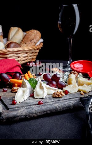 Cheese plate served with grapes, honey, nuts and glass of wine with bread basket on a wooden background. Various types of cheese. - Stock Photo