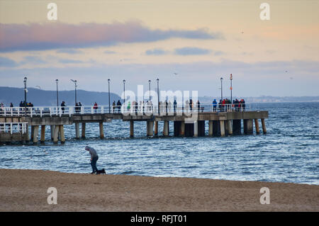 People strolling along a wooden pier stretching into the Baltic sea in Jelitkowo, Gdansk, Poland - Stock Photo