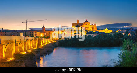 Panoramic view of Roman Bridge and Great Mosque (Mezquita cathedral) on Guadalquivir river at night. Cordoba, Andalusia, Spain - Stock Photo