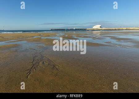 Matosinhos peaceful beach at low tide on a bright morning with interesting sand ripples in the foreground and the south of Leixoes harbor in backgroun - Stock Photo