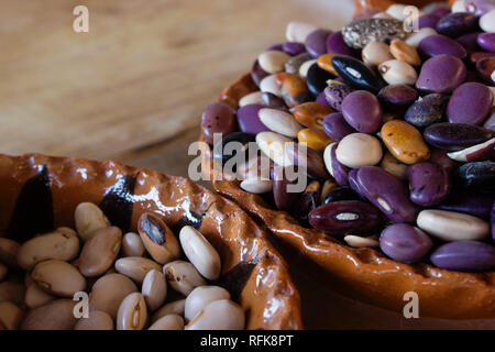close up of two handmade mexican clay pots with a wide variety of bean seeds - Stock Photo