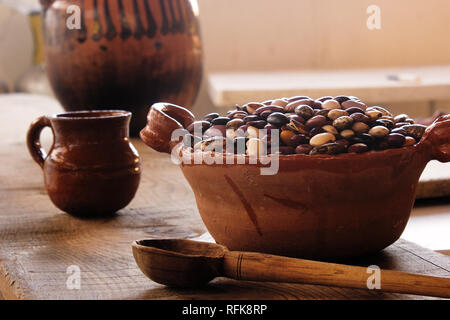 mexican hand made clay pot full with a wide variety of bean seeds, mexican clay dishes on a vintage rustic wood table and spoon - Stock Photo